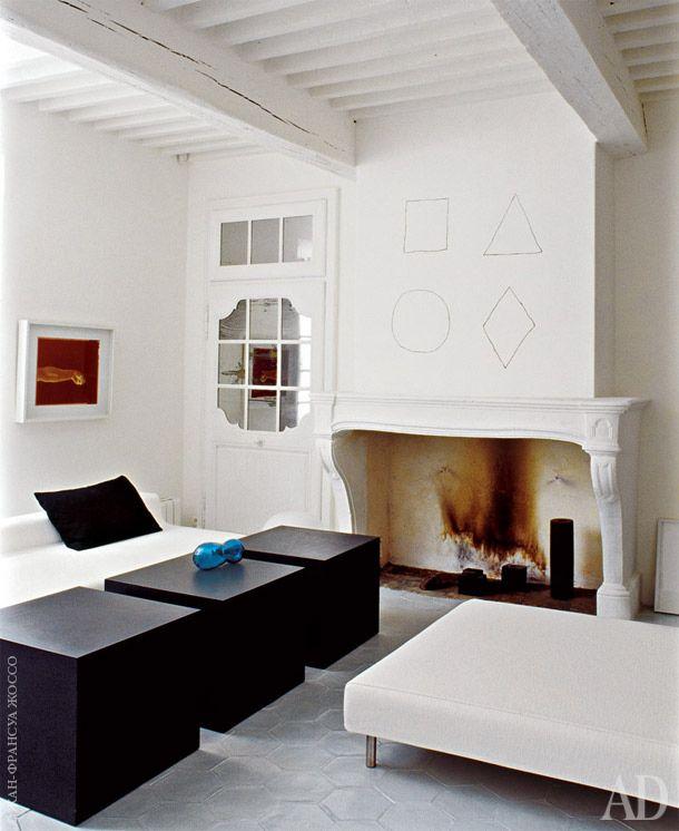 На стене над камином в гостиной — геометрическая композиция художника Сола Левитта. В самом камине стоят черные свечи.…