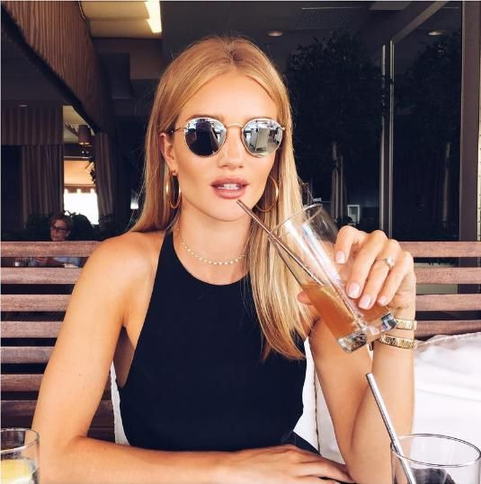 Rosie Huntington-Whiteley wearing Neil Lane Cushion Cut Diamond and Platinum Engagement Ring, Bvlgari Tubogas Watch, Mara Carrizo Scalise 14k Yellow Gold 24mm Classic Hoop Earrings, Ray-Ban Round Metal Folding Mirror Sunglasses and Jacquie Aiche 31 Diamond Emily Necklace