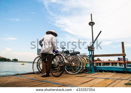 Hoi An, Central Vietnam. May 16, 2014 . Woman with bike on the ferry across the river in Hoi An - stock photo