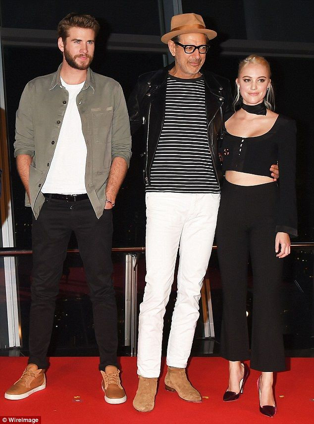 A day in the office: Liam Hemsworth (L)showed off a bushy beard on Wednesday as he attended the Independence Day: Resurgence's conference in Tokyo, Japan with Jeff Goldblum (M) and Maika Monroe (R)