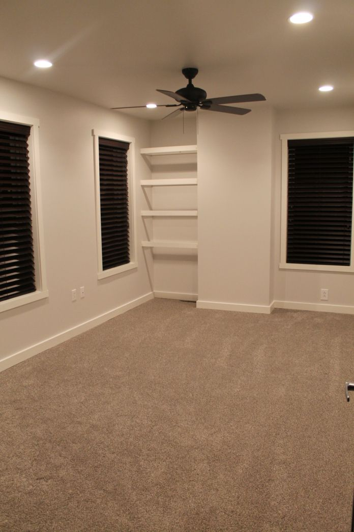 Clean, bright walls with a light gray carpet and dark wood blinds for our second bedroom remodel.