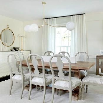 Elegant Dining Room Features A Modular White Glass And Brass Light Illuminating Salvaged Wood Table Lined With Gray Gustavian Chairs