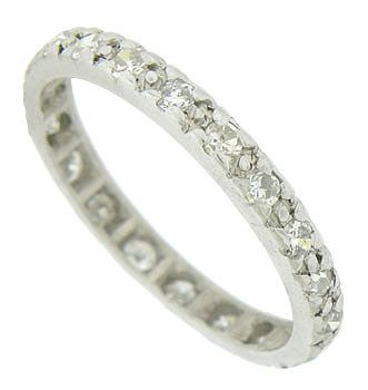 This antique platinum wedding band is set with a dazzling string of fine faceted diamonds. The round cut diamonds spin across the entire surface of this Art Deco wedding ring. The ring measures 2.65 mm in width. Circa: 1920. Size 7 3/4. We cannot re-size.
