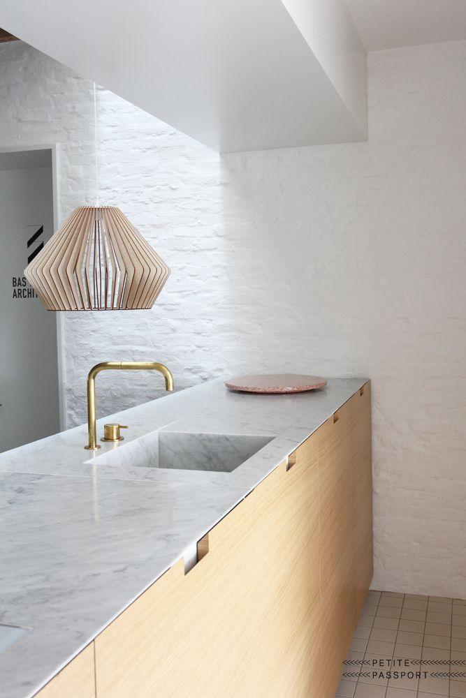Cuisine minimaliste : bois clair, façades lisses, marbre.