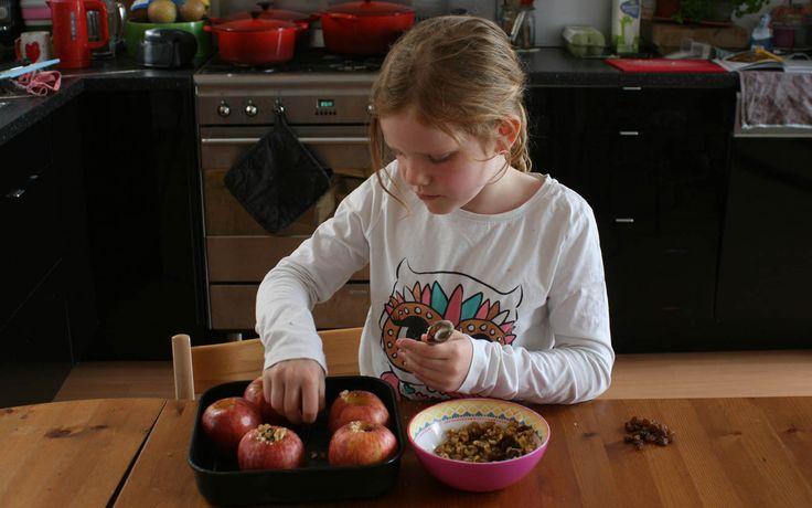 Annemijn is druk bezig om de appeltjes te vullen met walnoten, rozijnen en een beetje kaneel. Ze maakt 1 van haar favoriete toetjes: appeltje met vanillesaus.
