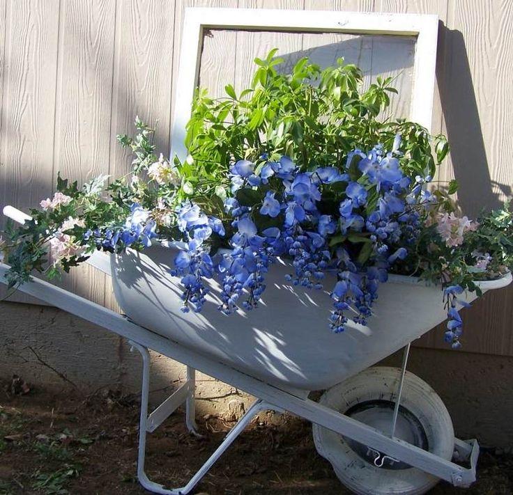 weiß bemalte Schubkarre mit Blumen als Gartendeko