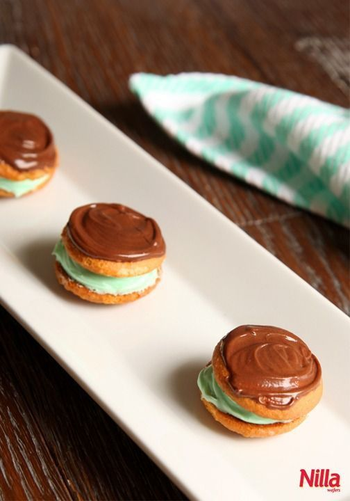 Mini Grasshopper Pies with Nilla Wafers! Sandwich mint frosting between two Nilla Wafers and spread chocolate on top for a tasty bite.