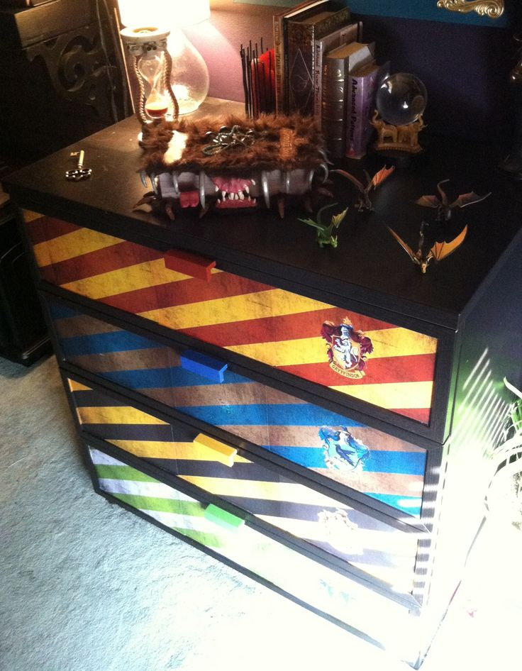 My Harry Potter dresser!! You jelly??  >.< **A lot of people have re-pinned my Harry Potter dresser lately so I thought I would share how easy it is to make.  I used Ikea's Hopen 4 drawer dresser; I found color patterns for the Hogwarts houses, and house crests online and printed them; I used ModPodge to glue the paper on the drawer fronts, then glued on the crests and painted the drawer handles to match. It's super easy!