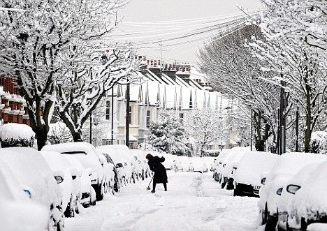 Snow-go zone: A hopeful commuter does her best to dig out her car in Chiswick, West London, 2009