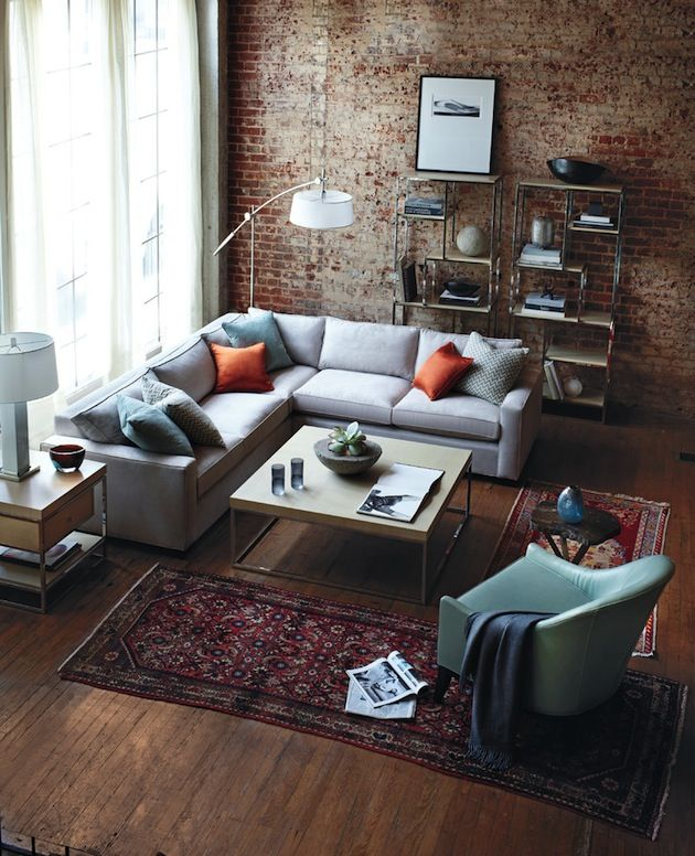 Brick wall, light grey couch, oriental rug, colorful throw cushions