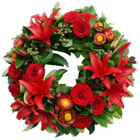 Red Asiatic lilies, roses, paper daisies and glossy green foliage make a traditional wreath fresh and bright.  Design : Flowers For Everyone, Sydney