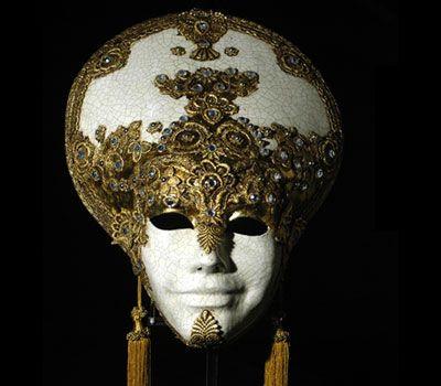 LIBERTY ORO SA22 - GOLDEN LIBERTY Maschera realizzata a mano in cartapesta. Decorata con foglia d'oro, tecnica dello screpolato, pizzo macramè ed impreziosita da cristalli Swarovski e perle. Spediamo in tutto il mondo.
