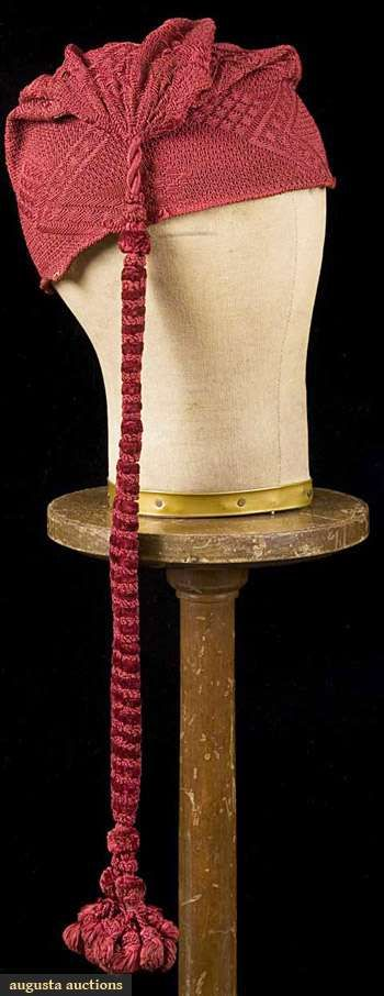 "RED SILK KNIT WORKMAN'S CAP, SARDINIA, 17TH C Dark red short cone shape, raised pattern of parallel zig-zags w/ single diamonds in between, larger diamonds on the outer corners of zig-zag design, Ht 9.23"", Wd 22"", at cap top extremely long, fancy cord made of rows of red chenille & silk balls, terminating in cord & tassels, L 18.5"""