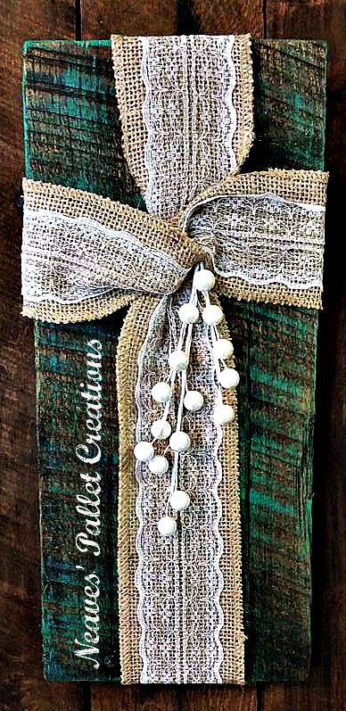 """RECYCLED WOOD PALLETS: This sweet rustic Cross is created with a loop of lace burlap. It is embellished with a sprig of off-white pearls. The Oak pallet board has been painted teal and then stained. Overall it is 12.5"""" tall x 6"""" wide. There is a wire loop on the back to hang it with. We are asking $8 for it. If you like it but want it in a different color, message us and we will customize one just for you. Please tag friends and share this if you like it. We appreciate the help. Item # 716"""