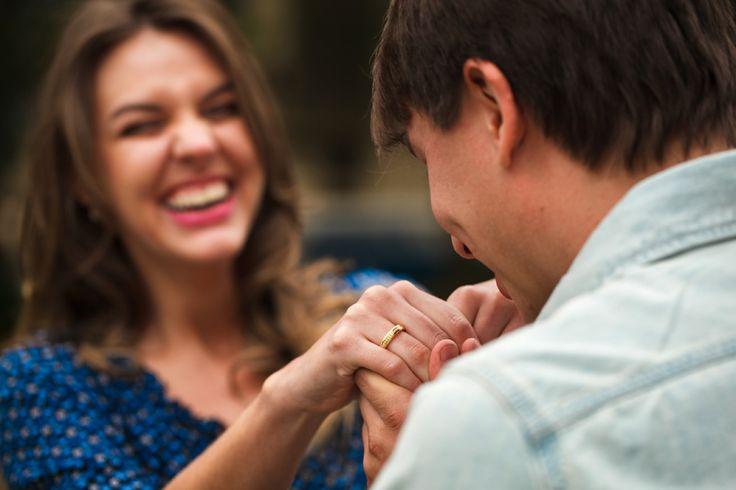 Pedido surpresa de casamento na praca em Curitiba. Noivo beijando a mão e a aliança da noiva