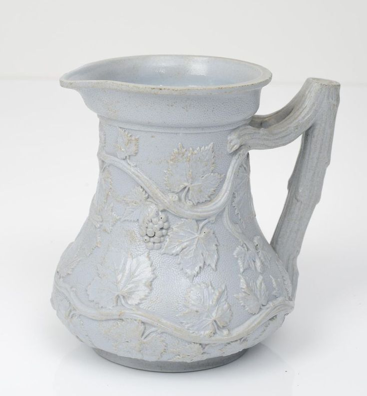 A very nice early Victorian jug by Minton.  It is of moulded form with vines and leaves associating it as a wine jug.  The handle is formed as a trunk and branches.  The glaze is a gloss blue/grey.  Moulded marks to the underside including a registration lozenge and details it as 'Society of Arts Prize Jug' and dated 1846.  M & Co mark to the underside, which is not commonly used by Minton, but found on some examples from this period.  Also carries the pattern number (302) in a cartouche.  A nic
