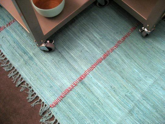This woman took several small area rugs (bought for 4 dollars at Target) and sewed them together with a simple stitch in a contrasting color. Very cool! And cheap! A large rug for less than 20 bucks!!