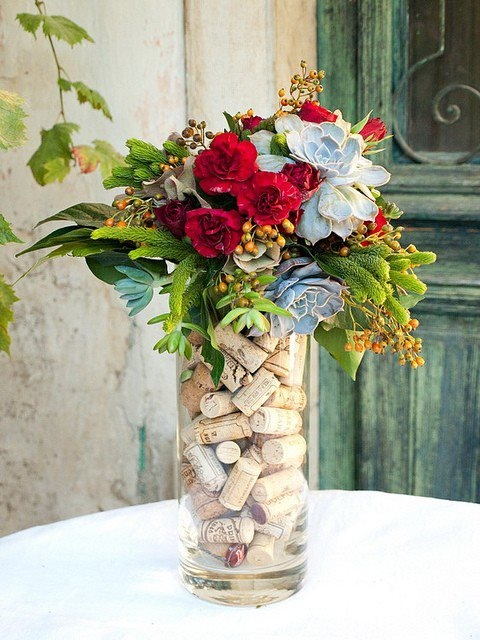 Put a smaller vase inside the larger and drop corks between the two.  Add water to the inner vase and fresh flowers and a center piece is yours.