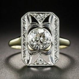 Five-eighths of an inch long and lustrous, this classic Edwardian dinner ring, hand-fabricated in platinum over 18K gold, sparkles front and center with a bright white and beautiful European-cut diamond weighing 1.10 carats. The bezel-set diamond seemingly floats inside a fanciful rectangular hand-engraved frame enlivened with a small diamond twinkling at each end. A distinctive original dazzler. Currently ring size 5 1/4.