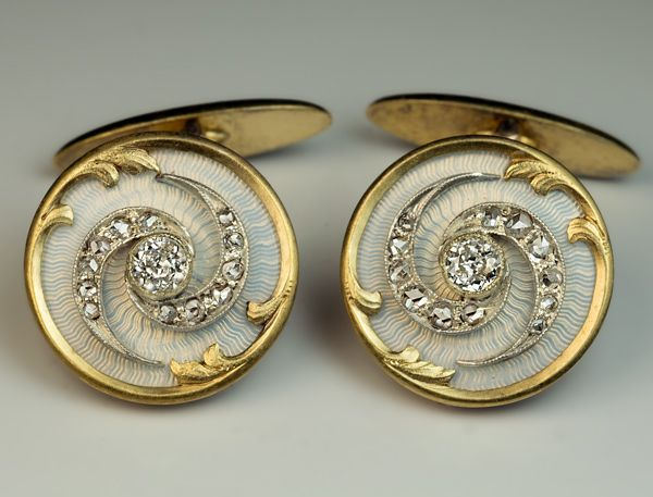 Antique Diamond, Enamel, Silver and Gold Cufflinks, St Petersburg, Maker's Initials 'BB', 1908-1917. A pair of superb Imperial era cufflinks of a tourbillon design, embellished with old European and old rose cut diamonds set in silver on a ground of an exceptional quality bluish-white guilloche enamel, within a gold Art Nouveau frame.