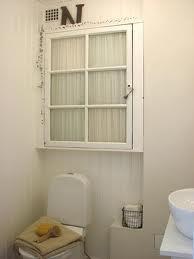 """badrumsskåp av fönster där man """"gömt"""" innehållet med en gardin"""
