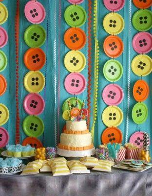 Voor dit Lalaloopsy feestje werden grote 'knopen' gemaakt van papieren borden. Vier zwarte cirkels erop simuleerden de knoopsgaten. De borden hingen met touwtjes aan elkaar. Zo slim! Idee