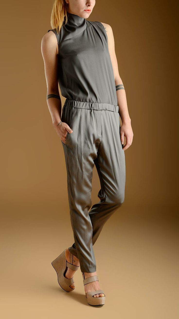 Grey silk jumsuit characterized by: a back key-hole turtle-neck top featuring an elasticized waistband in the upper side