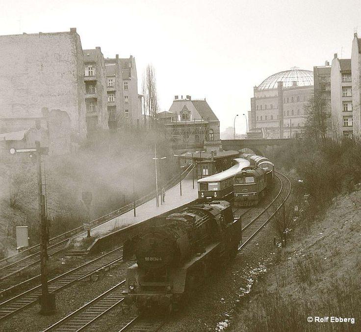 Rolf Ebberg: S-Bahn, Dampf und Diesel in Ostberlin 1980 - Hochbetrieb nahe dem Bahnhof Prenzlauer Allee. Die Öl-50er rollt zischelnd Richtung Rummelsburg, eine Maschine der Baureihe 120 (Chruschtschow's letzte Rache oder Taigatrommel) wartet mit ihrem Güterzug immer noch auf Freigabe der Strecke Richtung Norden und ein Zug der S-Bahn ist eben eingefahren.