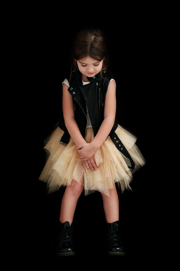 // Miss Kaira, the rebel princess, wearing gold tulle dress by Salzarra and Burberry leather biker vest