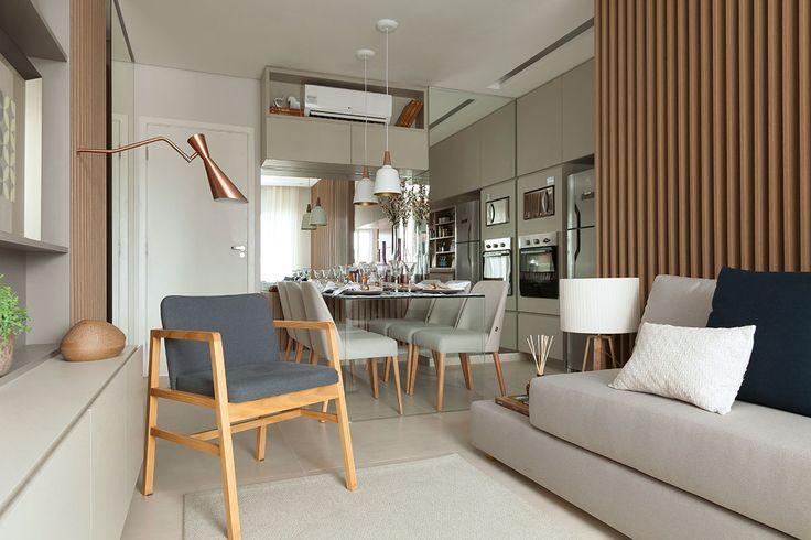 Decoração de apartamento pequeno e charmoso com ambientes integrados com ripas de madeira. Na sala de jantar mesa de jantar de vidro retangular, cadeira estofada, pendente e flores. Na sala sofá, cadeira de madeira, luminária de parede e almofadas.