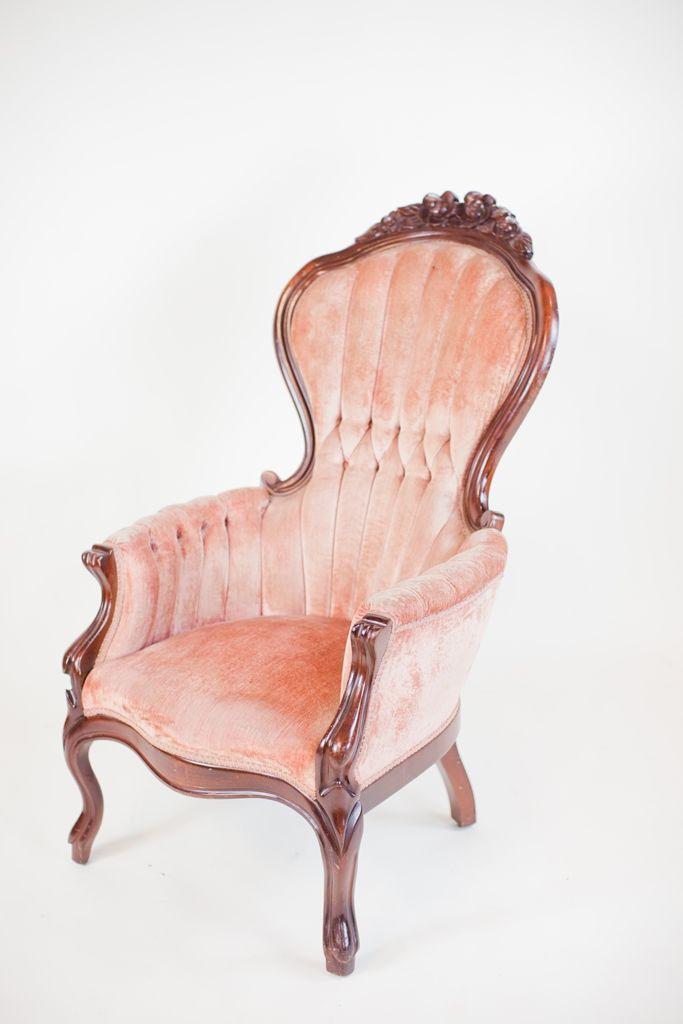 blush pink velvet tufted victorian chair with dark wooden frame.
