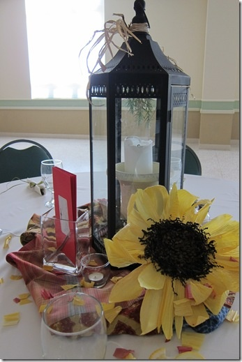 Lanterns with sunflowers. It'd be pretty with the sunflowers in a ring all around the base of the lantern