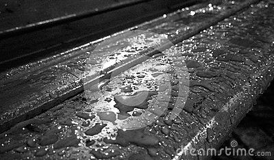 A black and white shot of rain drops on a wooden bench at night.