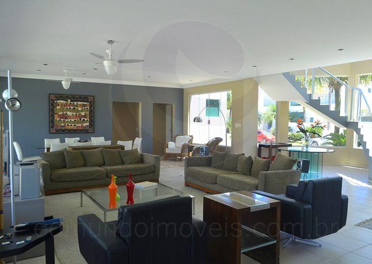 Valorizada pela iluminação natural, a sala de estar conta com ótima iluminação. Poltronas em couro foram combinadas ao conjunto de sofás revestido em sarja verde oliva, uma opção muito versátil para o ambiente praiano.