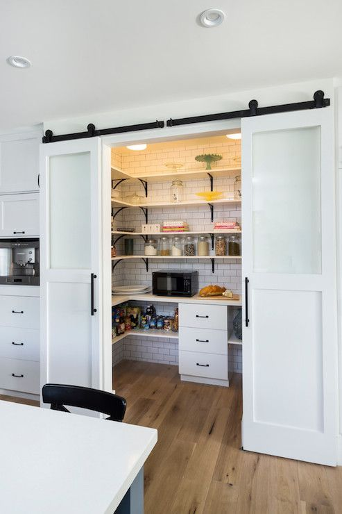 U shaped walk-in pantry with glass front barn track doors, stacked shelving accented with black iron corbels on ceiling height subway tiled wall as well as microwave over wood floors next to built-in coffee machine.: