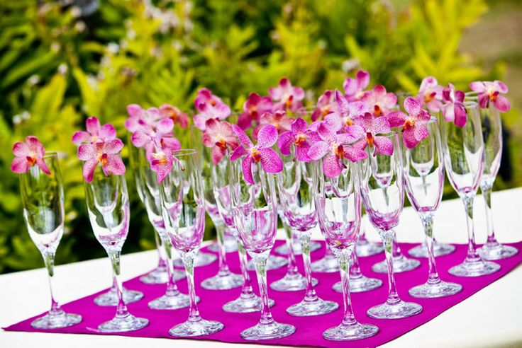 Orchids for pretty champagne glasses. See more: http://modernweddingshawaii.com/chic-pinks-from-yvonne-design/