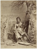 Clarence River - Young man, seated, with axe and boomerangs and fur rug, by bark shelter