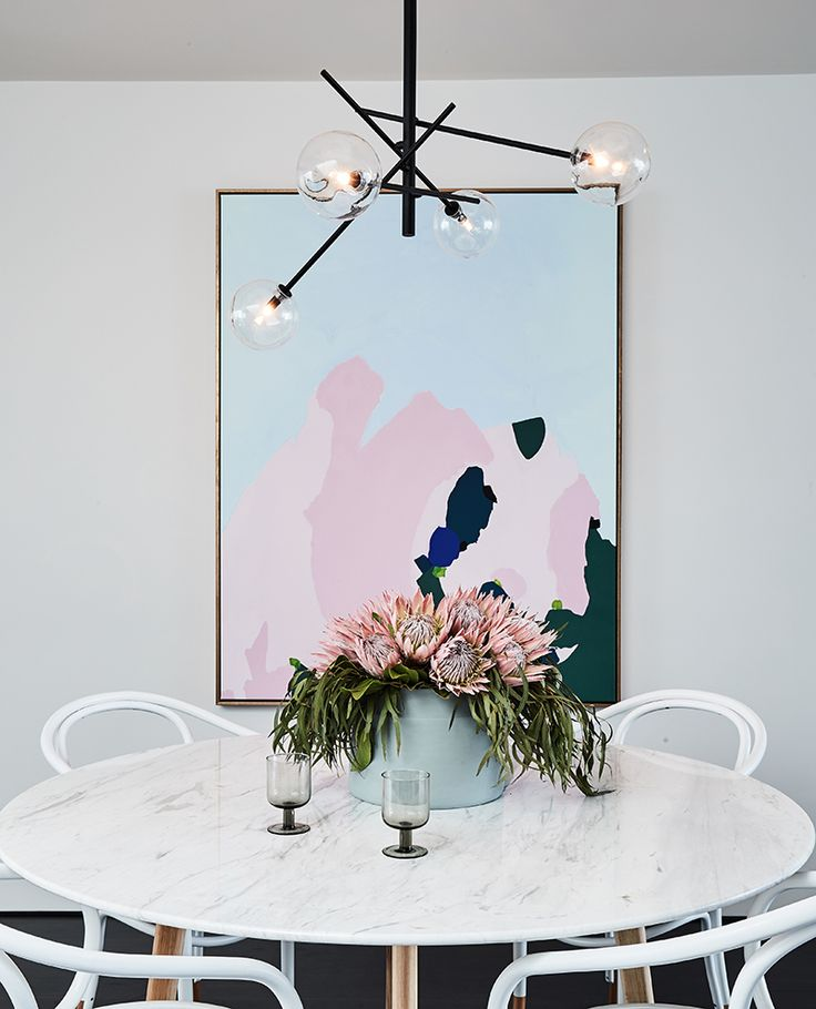 Dining - gloss white marble round dining table with wooden legs, white Thonet bentwood armchairs, black branch lights, blue and pink pastel painting artwork