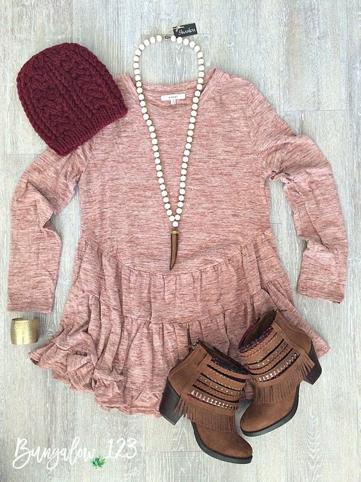 Super soft and cozy melange knit top featuring a ruffle placket along bottom. Looks great with denim or jeggings for cool weather! Shown with the Tally Booties in Cognac, Ivory/Tusk Shanlou Necklace,