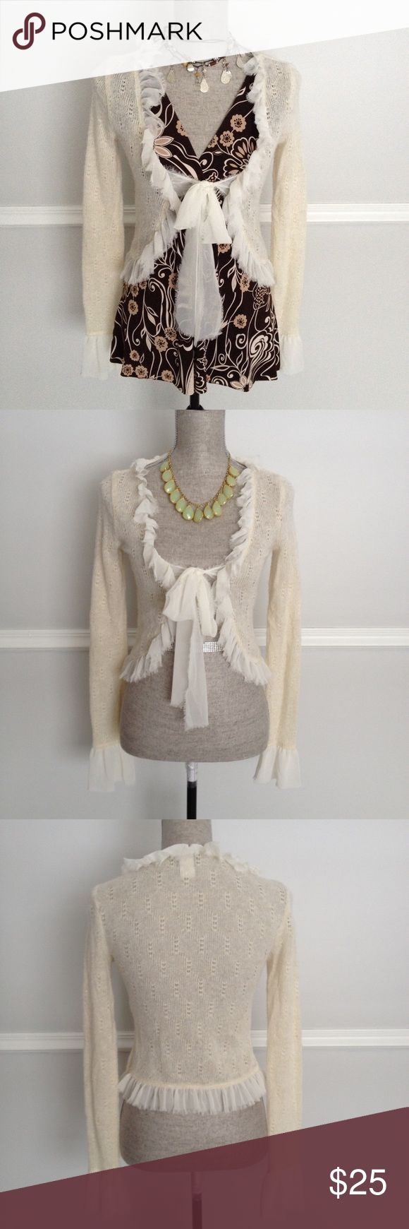 Exquisitely Chic Shrug This very subtle shimmery cardigan sweater/shrug has a lightweight & delicate feel with its loosely woven fibers of cream and a subtle strand of gold thread and adorned with creamy sheer, frayed-bottom ruffles.  Very versatile and would literally go with anything from casual to dressy.  It's a small but I would say it runs small, more like an extra small. (Machine washable) Daytrip Sweaters Cardigans