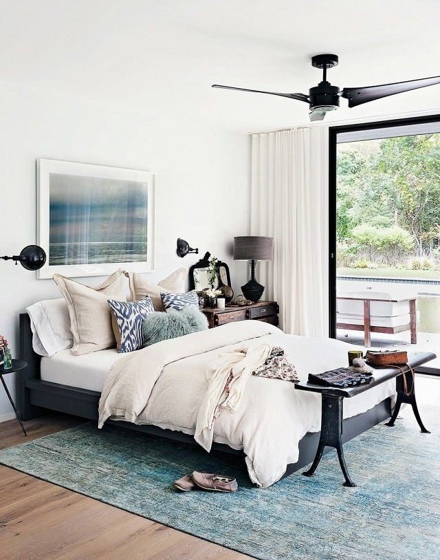 Calm bedroom with an IKEA bed frame, white bedding, and blue accents