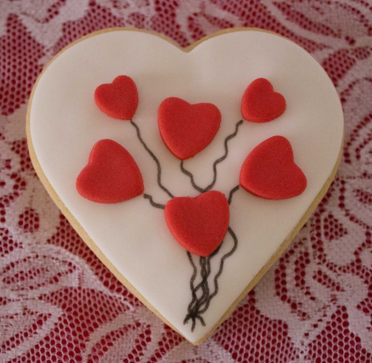 Cute little floating heart balloons on a heart shaped sugar cookie