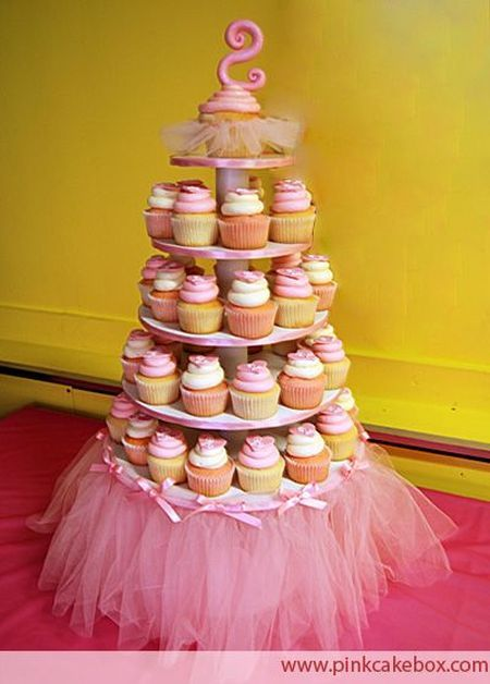 1st girl birthday cupcake tower featuring tulle, ribbons and bows.  See more first girl birthday party ideas at www.one-stop-party-ideas.com