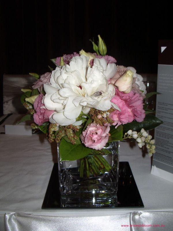 RG8 Small floral posy arrangement in a cube vase sitting on a mirror base. Soft and feminine blooms in pinks and whites.