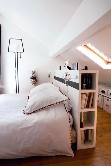 Using a bookshelf to ground a bed in the middle of the room, so another distinct space is created behind it.