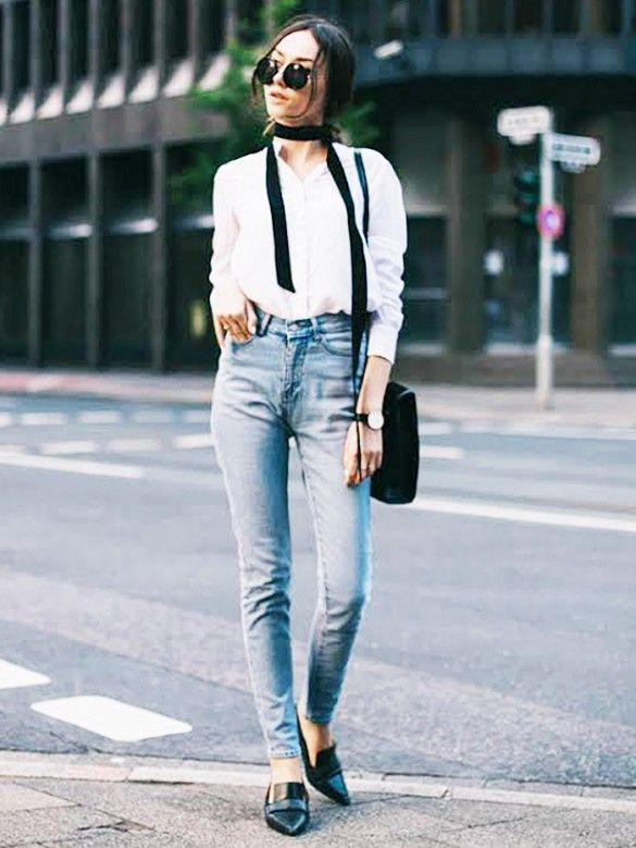 A white button-down shirt is worn with high-waisted jeans, loafers, a skinny scarf, and round sunglasses