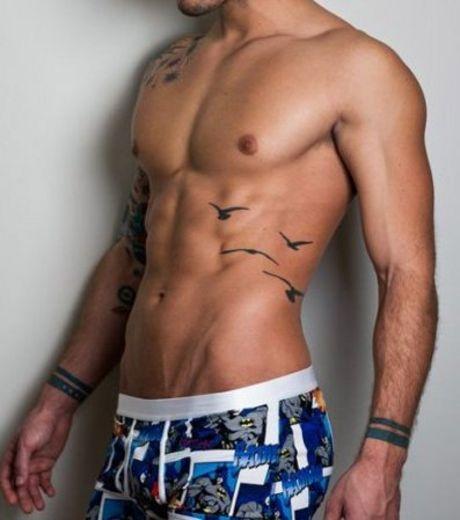 Tatouage oiseau sur la hanche d'un homme