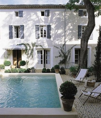 Simple white exterior with gray shutters, potted boxwoods, and pool