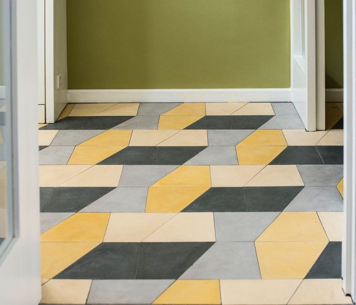 Even in bright colors, cement tile has a muted, chalky appearance. Here, an entryway composed of black, blue, yellow, and tan tiles from Huguet's Plain Tile collection, in a combination created by Slovakian graphic designerPeter Biľak.