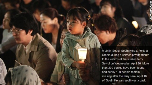 A girl in Seoul, South Korea, holds a candle during a service paying tribute to the victims of the sunken ferry Sewol on Wednesday, April 30. More than 200 bodies have been found and nearly 100 people remain missing after the ferry sank April 16 off South Korea's southwest coast CNN.